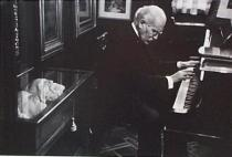 Arturo Toscanini in his home. The glass-covered cabinet holds death masks of Beethoven (partly shown), Wagner, and Verdi. Milan, 1954
