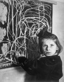 """Terezka, a disturbed child in an orphanage. The scrawl on the blackboard is her drawing of """"home"""". Poland, 1948"""